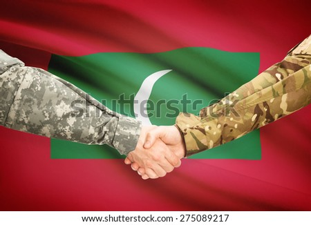 Soldiers shaking hands with flag on background - Maldives - stock photo