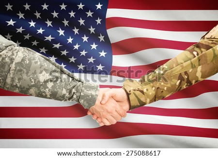Soldiers shaking hands with flag on background - United States - stock photo
