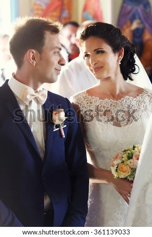 Solemn moment of marriage newlyweds in the church. Beautiful smiling brunette bride and handsome groom. - stock photo