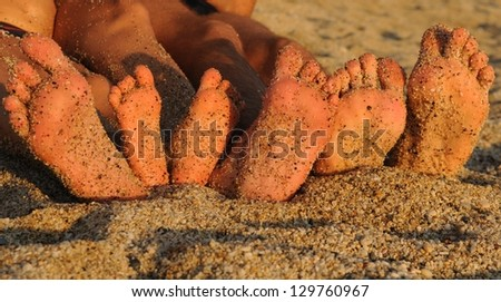 Soles of a sunbathing family on a pebble beach - stock photo