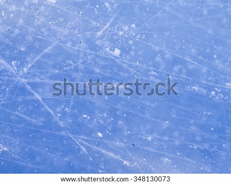 solid blue beautiful ice skating rink in winter and a lot of traces of runners skates outdoors - stock photo