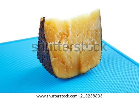 solid cheddar cheese on blue plastic board - stock photo