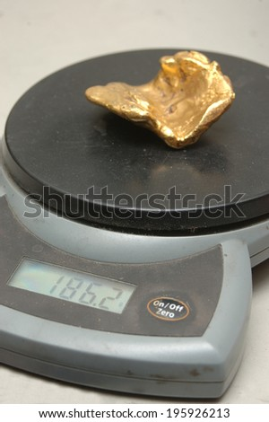 solid gold nugget on jeweller's scales - stock photo
