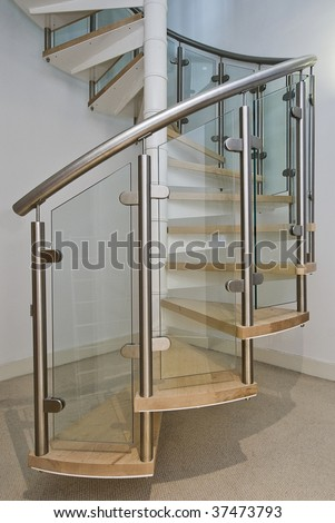solid newel stairs with wooden steps, and glass and steel rail - stock photo