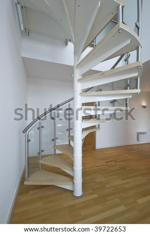solid newel stairs with wooden steps and glass and steel rail - stock photo