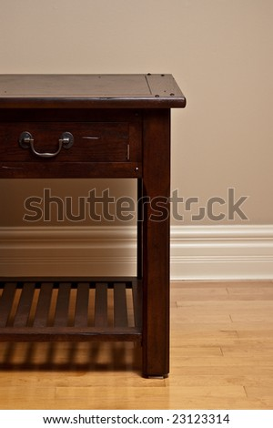 Solid wood end table against earth tone wall and hardwood floor. - stock photo