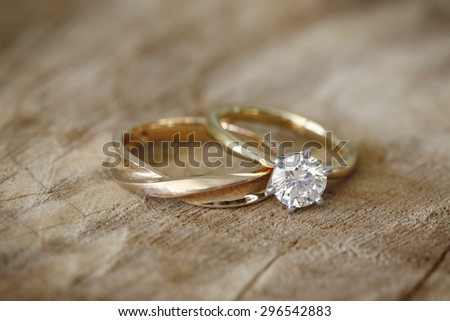 Solitaire engagement diamond ring with wedding band on wooden organic background.  - stock photo