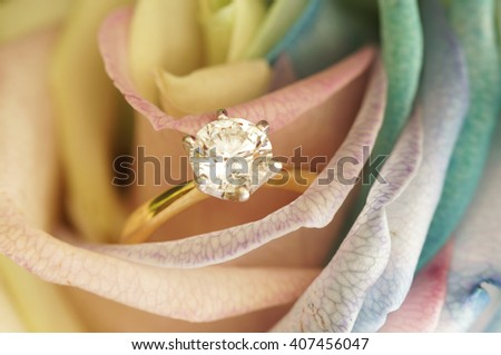 Solitaire ideal cut diamond ring in the midst of yellow rose. - stock photo
