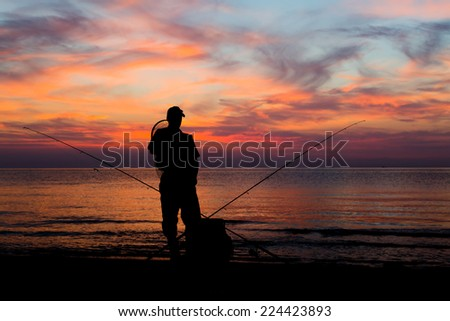 Solitary fisherman waiting for the next catch with the faded sun hovering on the horizon. - stock photo