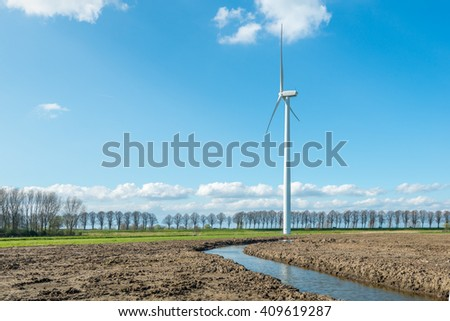 Solitary wind turbine in a rural area in the Netherlands. The huge height of the mast is striking with respect to the height of the row of trees in the background. - stock photo