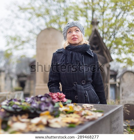 Solitary woman mourning with her hand on gravestone, remembering dead relatives in on Pere Lachaise cemetery in Paris, France. - stock photo