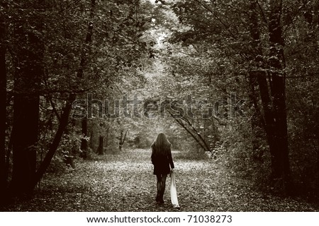 Solitude concept - lonely sad woman in the woods - stock photo