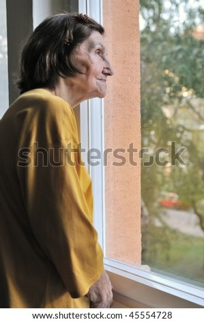 Solitude concept  - sad 80s senior woman looking through window at home - stock photo