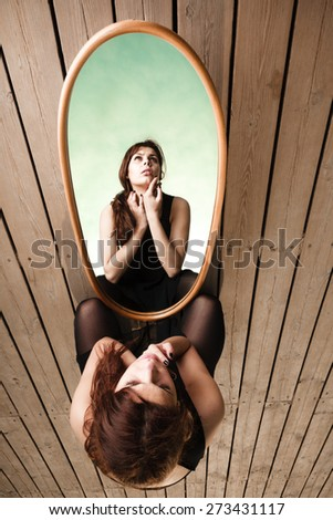 Solitude loneliness concept. Thoughtful young woman looks at the reflection in the mirror outdoors on pier - stock photo