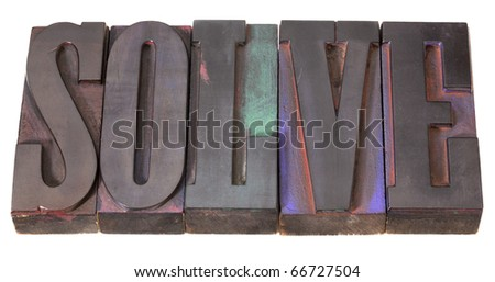 solve word in antique letterpress printing blocks, stained by color inks, isolated on white - stock photo