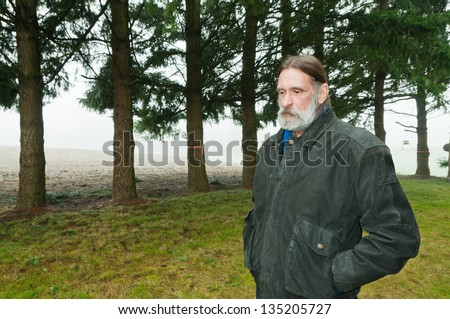 Somber Middle Aged Man standing outside with hands in pocket. Row of evergreen trees in background. Copy space. - stock photo