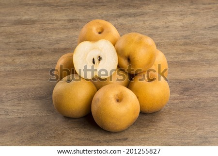 Some asian pears over a wooden surface - stock photo
