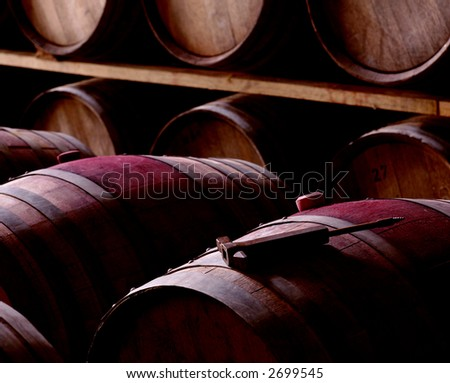 some barrels in a winery, one of them with some tool over it - stock photo