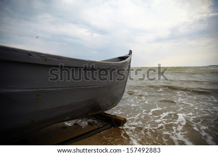 Some boats at the seashore on a cloudy day - stock photo