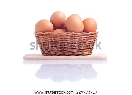 some brown eggs in a basket on a small cutting board isolated on white background with reflection side view - stock photo