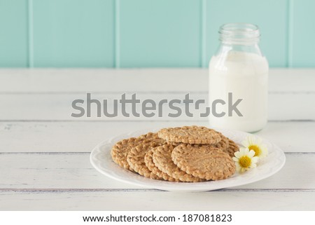 Some cereals cookies, a school milk bottle and a apple on a white wooden table with a robin egg blue background. Vintage - stock photo