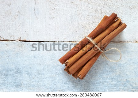 Some cinnamon sticks tied with a natural rope, on a white wooden table. Top view - stock photo