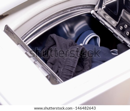 Some clothes in the washing machine top loading - stock photo