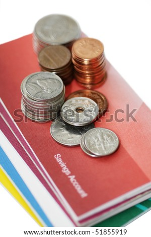 Some coins on savings account passbook. - stock photo