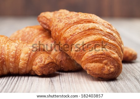 Some croissants on a wooden surface - stock photo
