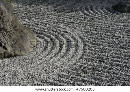 Some detail of a Zen garden in Kyoto.  The gravel has been raked by monks.  These gardens typically contain sand or gravel and bare stones. - stock photo