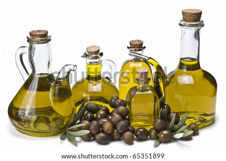 Some different bottles of olive oil and some olives isolated on a white background. - stock photo