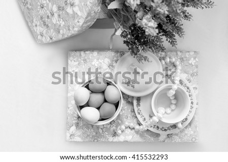 Some dishes with painted easter eggs and pearls on a book with lavender flowers on white background - stock photo