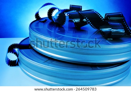 some film strips and metal movie film reel canisters on a table with a blue toning - stock photo