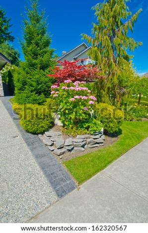 Some flowers and nicely trimmed bushes on the front yard in the suburbs of Vancouver, Canada. Landscape design. - stock photo