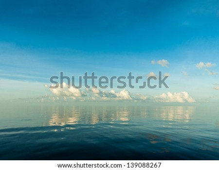 some fluffy clouds reflecting over a calm sea - stock photo