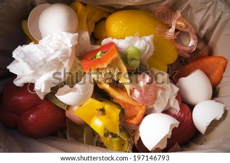 Some foods items including egg shells and vegetables in the trash can. - stock photo