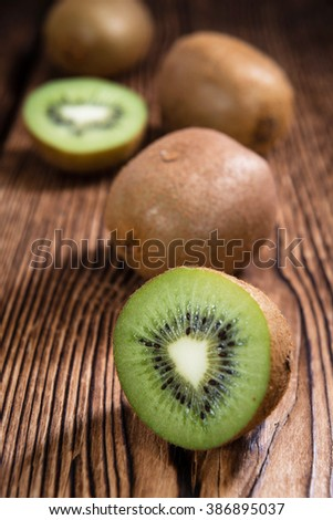 Some fresh Kiwi Fruits (selective focus) on an old wooden table - stock photo
