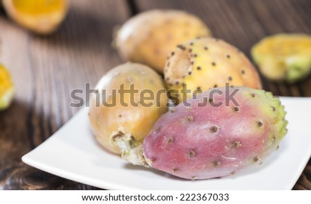 Some fresh Prickly Pears on wooden background (close-up shot) - stock photo