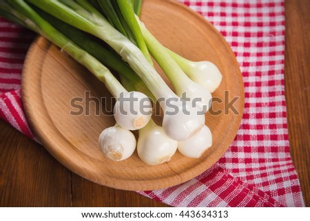 some fresh raw ripe green onion on wooden background - stock photo