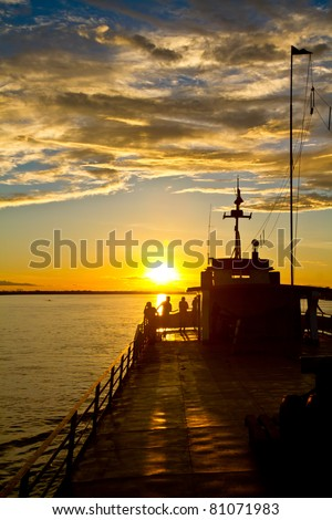 Some friends enjoy the last light on the Amazon river. - stock photo