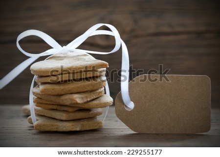 Some Ginger Bread Cookies with white Ribbon and Bow and a Label with Copy Space, on wooden Background - stock photo