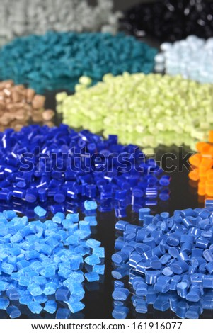 some heaps of dyed polymer granulate for injection moulding - stock photo