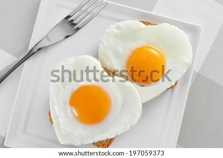 some heart-shaped fried eggs on toasts in a plate, on a set table - stock photo