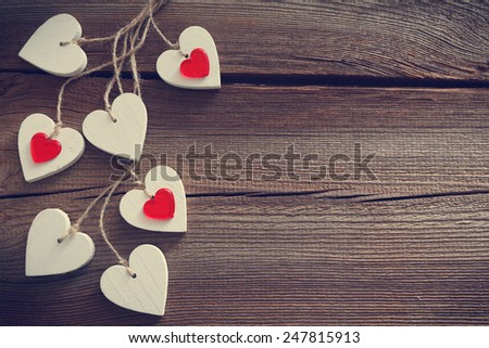 some  hearts hanging in front of wooden board for valentines day - stock photo