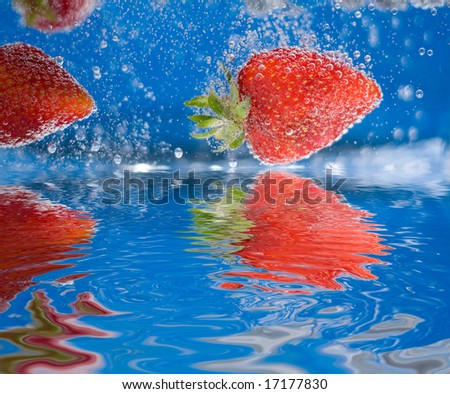 Some juicy red strawberries plunging into some water with reflections. - stock photo