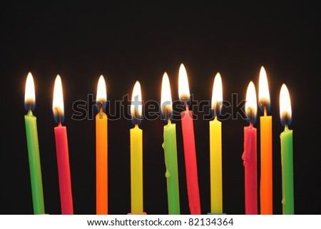 Some lit birthday candles close up , shallow dof - stock photo