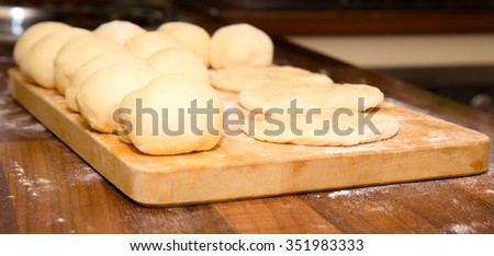 Some lumps are already rolled in flat cakes and are ready to filling  and to transformation into pies - stock photo
