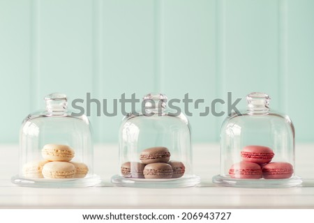Some macarons in three glass bell jars on a white wooden table with a robin egg blue background. Vintage Style. - stock photo