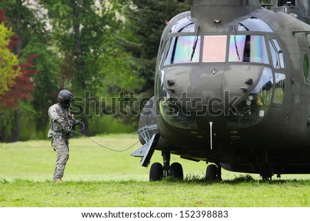 Some natural and man made disasters require rescue services. This is a Chinook helicopter being used in a mock disaster relief rescue to transport victims from a park grass field to the hospital. - stock photo