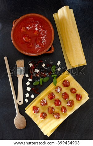 Some of ingredients used to prepare lasagna following an old recipe from Naples: lasagna sheets, small meatballs in tomato sauce, small pieces of mozzarella cheese, grated parmesan cheese, basil. - stock photo